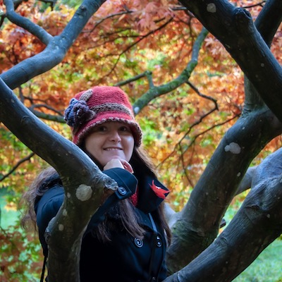 My Autumn Bucket List To Welcome In The New Season, Corinna surrounded by autumnal trees at the arboretum